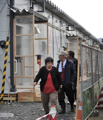 Image: Evacuees walk in front of their temporary housing