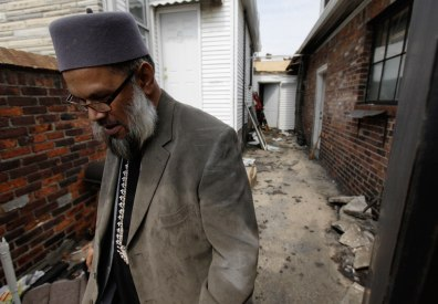Image: Imam Abdul Latif Azom walks past damage from an April 1, at the Masjid Al-Falah Islamic Center of North Detroit