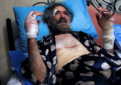 Image:Wounded Syrian cartoonist Ali Farzat rests in bed at his residence in Damascus