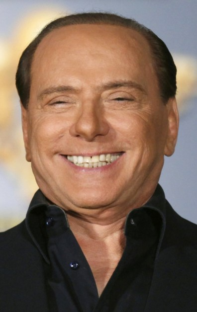 Image: Italy's Prime Minister Berlusconi smiles as he attends the Atreju political meeting in Rome