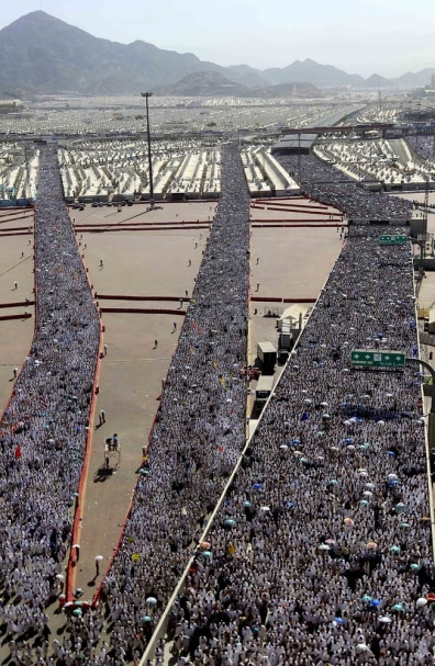 Image: A crowd of Muslim pilgrims make their way to throw cast stones at a pillar, symbolizing the stoning of Satan