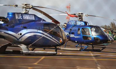 Image: A pair of Blue Hawaiian tour helicopters sit grounded at Kahului Airport in Maui, Hawaii