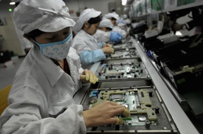 Image: Chinese workers assemble electronic components at the Taiwanese technology giant Foxconn's factory in Shenzhen