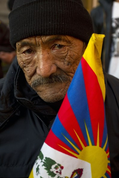 Image: An elderly Tibetan refugee holds a Tibetan flag ahead of a vigil in Dharmsala, India, to protest China police violence