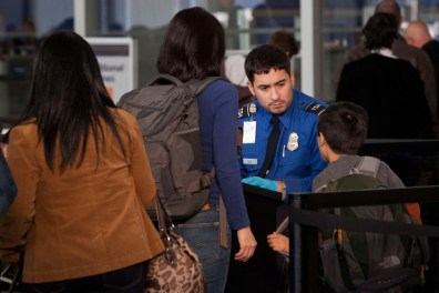 Image: A Transportation Security Administration official scans travelers at Terminal Five of John F. Kennedy Airport