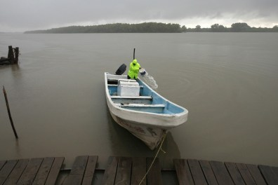 Image: A fisherman removes water out from his boat