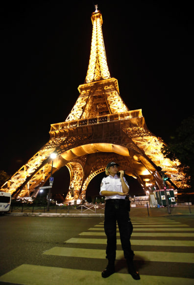 Image: A police officer stands in front of the Eiffel Tower