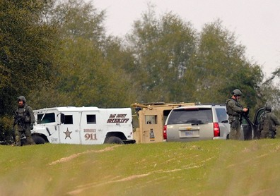 Image: Armed law enforcement personnel station themselves near the property of Jimmy Lee Sykes.