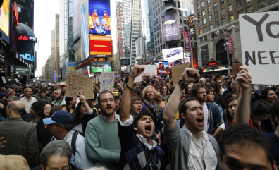 Image: Occupy Wall Street protesters shout slogans during a protest at Times Square in New York