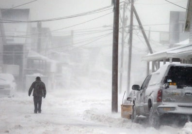 Image: A man walks in the snow down a road along the shore in Scituate, Mass., Friday, Jan. 3, 2014. A winter storm slammed into the U.S. Northeast with howling winds and frigid cold, dumping nearly 2 feet (60 centimeters) of snow in some parts and whipping up blizzard-like conditions Friday. (AP Photo/Michael Dwyer)