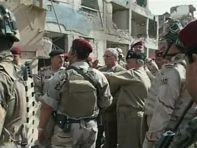 Image: Iraqi Defense Minister Abdul-Qadir al-Ubaidi, center, inspects the site of a suicide attack