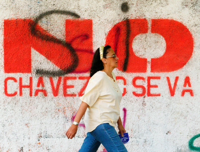 Woman walks past referendum graffiti in Caracas