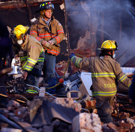 Image: Firefighters search through rubble