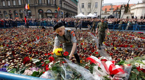 Image: Woman lays flowers on square near the Presidential Palace in Warsaw