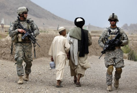 Image: Villagers pass US soldiers on patrol in Kandahar region
