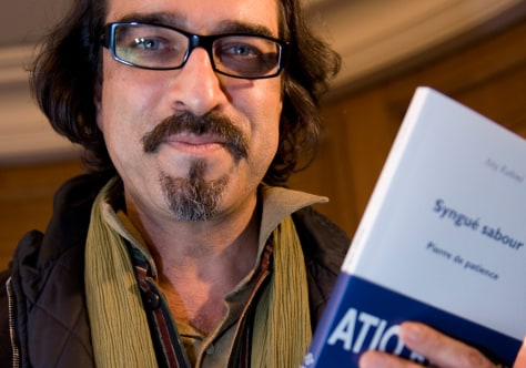 Image: Afghan author Rahimi poses with his book Syngue Sabour