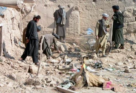 Image: Afghan men examine a destroyed house