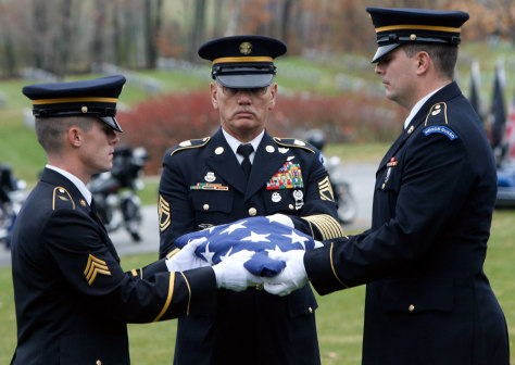 Image: An honor guard folds a flag during a ceremony