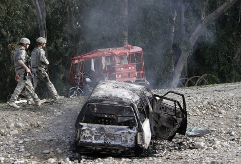 Image: U.S. soldiers walk past a destroyed car