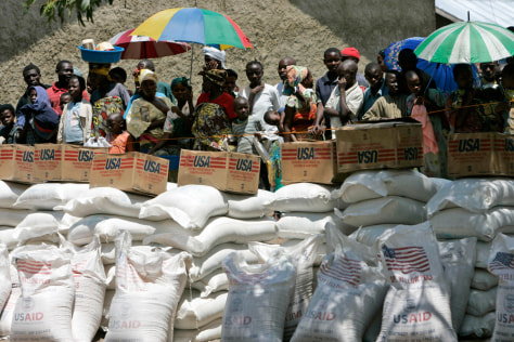 Image: Displaced people wait their turn to receive food aid