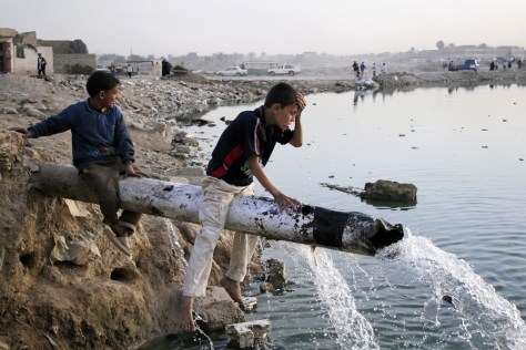 Image: Iraqi boy washes face from burst water pipe