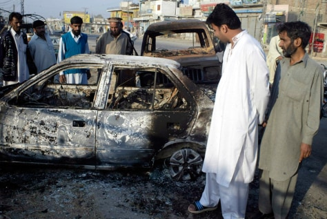 Image: People inspect a blast site in Dera Ismail Khan