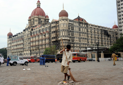 Image: An Indian worker sweeps the street in front of the Taj Mahal Hotel.
