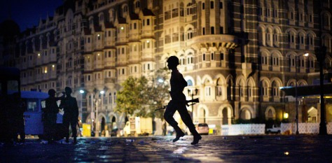 Image: An Indian soldier runs to take cover in front of the Taj Mahal hotel