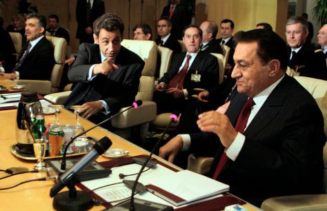 Image: French President Nicolas Sarkozy, center, gestures as he chairs with Egyptian President Hosni Mubarak