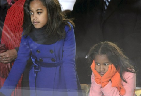 Malia and Sasha Obama watch the Inaugural Parade from their father's reviewing stand in Washington on Tuesday.