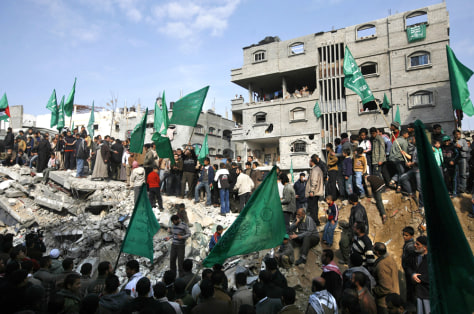 Image: Palestinian men wave Hamas flags