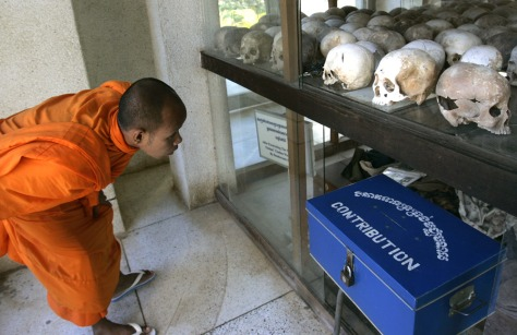Image: Monk looks at skulls