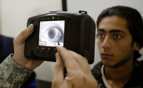 Image: A U.S. soldier akes a retina scan of a refugee