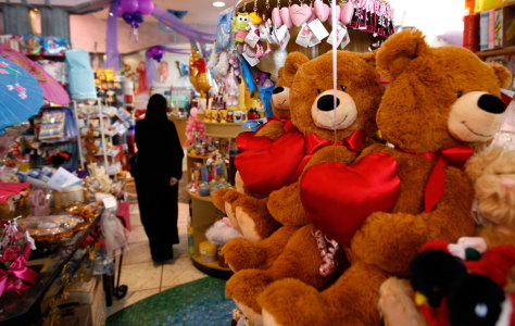 Image: A Saudi woman tries to choose a Valentine's Day teddy bears at a gift shop in the Saudi capital Riyadh, Saudi Arabia