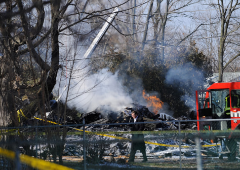 Image: An investigator walks through the scene of a Continental Airlines crash