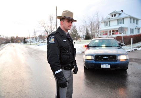 Image: A New York State Police officers mans a road block in a neighborhood near the crash site of a Continental Airlines flight.