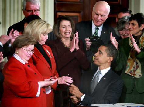 Image: President Barack Obama hands Lilly Ledbetter a pen