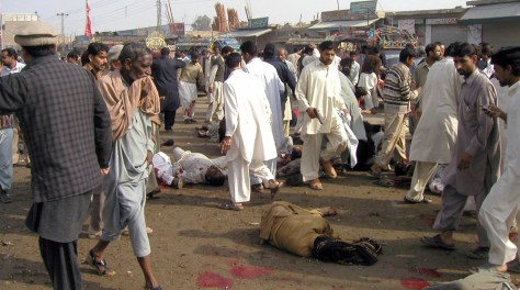 Image: People look at victims of suicide bombing in Pakistan
