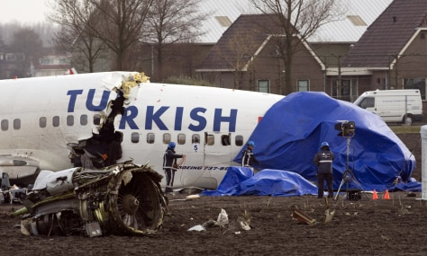 Image: Firefighters remove tarps from the wreckage of the Turkish Airways jet