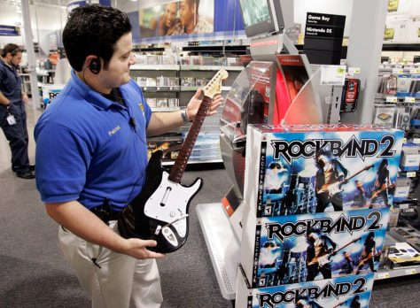 "Image: A worker holds up a guitar as part of the ""Rock Band 2"""