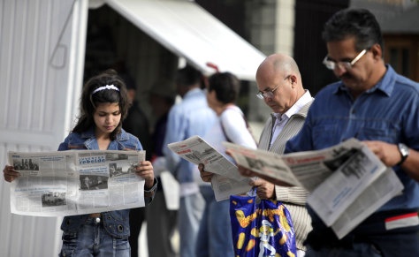 Image: People read Granma and Juventud Rebelde newspapers