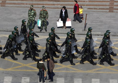 Image: Heavily armed paramilitary police patrol a street of Kangding