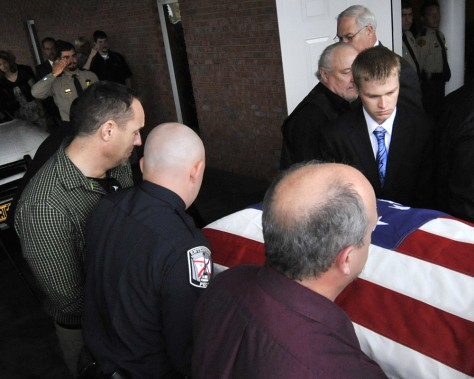 Image: Sheriff's deputy Josh Myers, upper right, salutes the casket bearing his wife and 18-month-old daughter