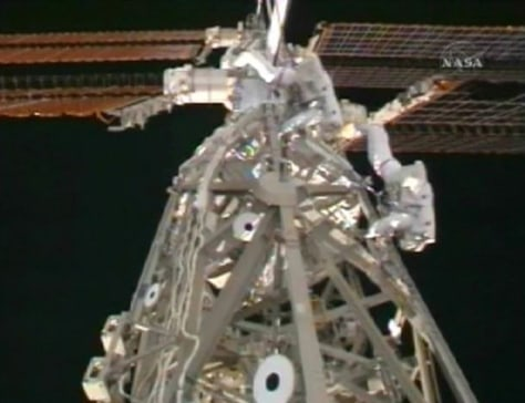 Astronauts Joseph Acaba and Steve Swanson work on cargo attachment system in this image from NASA TV