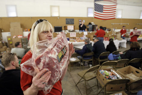 Image: Janet Cool displays frozen meet during the grocery auction