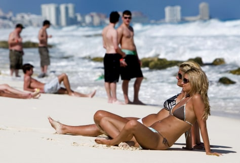 Image: Tourists rest at Cancun beach