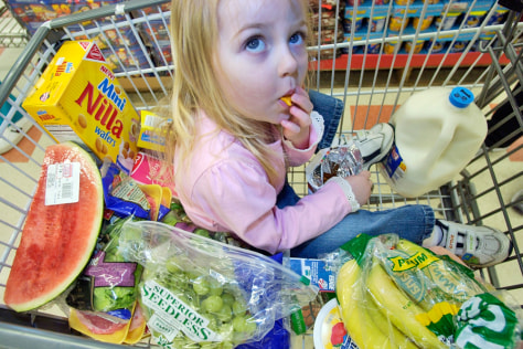 Image: Girl eats a snack in a grocery cart.