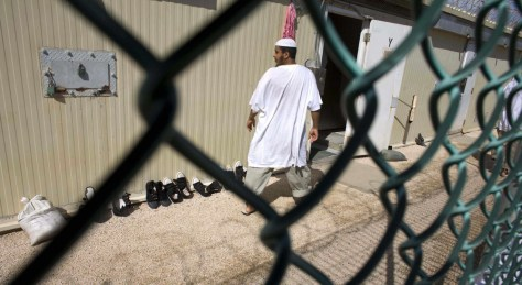 Image: Guantanamo detainee walks past a cell