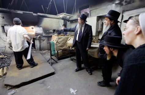 Image: Rabbi Beryl Epstein, center, explains the process of baking matzo