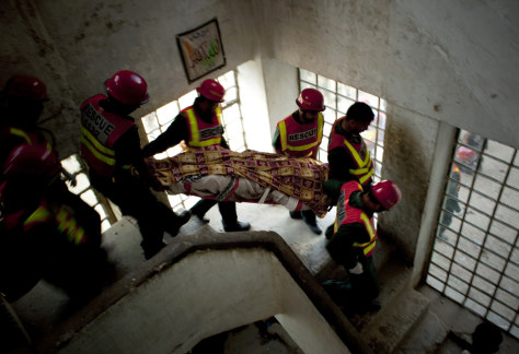Image: Pakistani rescuers carry the body a police officer